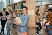 Smiling student holding books with friends talking in college library