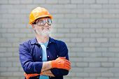Portrait Of Happy Seniorman With Hard Hat Posing With Crossed Arms