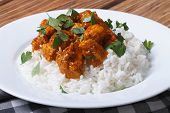 foto of curry chicken  - Chicken curry with rice and cilantro on white plate close up horizontal - JPG