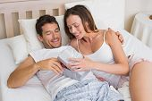 Relaxed young couple with gift box lying together in bed at home