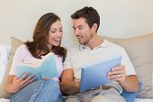 Relaxed happy young couple with laptop and book sitting on couch at home