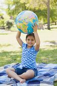 Full length portrait of a cute young girl holding globe at the park