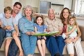 Portrait of happy multigeneration family with storybook at home