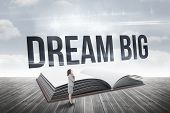 The word dream big and smiling thoughtful businesswoman against open book against sky