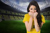 Nervous football fan in brasil tshirt in a large football stadium with fans in yellow