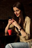 Portrait of young woman sitting relaxed at a cafe drinking coffee and chatting using her cell phone