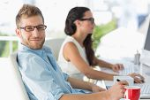 Handsome designer smiling at camera at desk in creative office