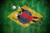Fit goal keeper jumping up against brazil flag in grunge effect