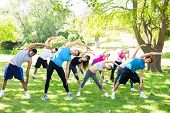 Full length of people doing stretching exercise in the park