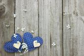 Blue and wood hearts with spring tree blossoms border wood fence