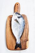 Delicious fresh dorado fish on wooden kitchen board