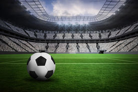 pic of football pitch  - Black and white leather football in a vast football stadium with fans in white - JPG