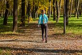 Nordic walking adventure and exercising concept - woman hiking withnordic walking poles in autumn park