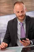 Businessman sitting in office, using mobilephone.