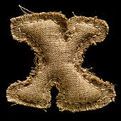 Linen or hemp vintage cloth letter X isolated on black background