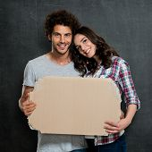 Young Beautiful Couple Holding Cardboard Over Gray Background