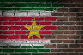 stock photo of suriname  - Very old dark red brick wall texture with flag  - JPG