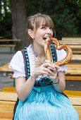 Young Woman In Dirndl With Pretzel