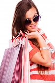 Young beautiful brunette with sunglasses holding shopping bags over shoulder, isolated on white