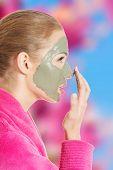 Beautiful woman in pink bathrobe and havinf facial mask.