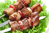 Grilled kebab (shashlik) on spits on the lettuce leaves.