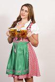 Woman posing in dirndl dress holding beer glasses