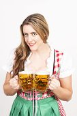 Woman posing in dirndl dress against a white wall.