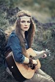 stock photo of hippies  - Beautiful hippie girl with guitar sitting on grass near stone