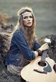 image of hippy  - Beautiful hippie girl with guitar sitting on grass near stone - JPG