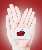 image of two hearts  - Male and female hands holding card with two hearts - JPG