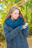 Young woman in a warm knitted blue ensemble using a mobile phone outdoors in autumn as she stands am