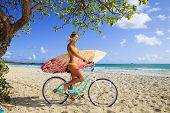 girl on a bicycle with surfboard