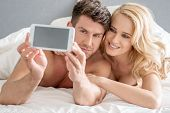 Middle Age Romantic Lovers Taking Sweet Photos on Bed with White Cover.