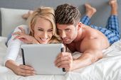 Young couple lying side by side on their stomachs reading a tablet in bed
