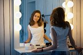 Beautiful Young Woman Looking At Her Reflection In A Dressing Room Mirror