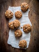 stock photo of baked raisin cookies  - Homemade oatmeal cookies with raisins and peanuts on a rustic wooden table - JPG