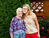 image of kindness  - Beautiful teenager granddaughter visiting kind grandmother at the nursing home - JPG