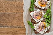 pieces of bread with cheese, tomato and onion on grilled crusty bread on wooden background