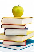 an apple lying on a pile of books. symbol photo for healthy and vitamin rich food in the school break.
