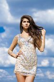 Young beautiful girl posing on blue sky background