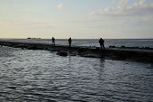 Fisher's silhouettes at pier