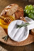 Camembert cheese, bread, honey and grapes on cutting board on wooden background