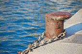 picture of bollard  - a rusty bollard with a metal chain - JPG