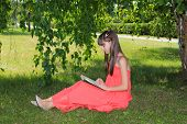 Girl in nature in a red dress is reading a book
