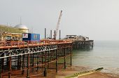 HASTINGS, ENGLAND - SEPTEMBER 20, 2014: A 39mtr crane mounted on a jack-up barge takes part in the reconstruction of the Victorian pier. Wrecked by fire in October 2010, the pier will re-open in 2015.