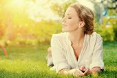 stock photo of lie  - Beautiful smiling woman lying on a grass outdoor - JPG