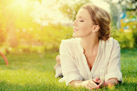 pic of grass  - Beautiful smiling woman lying on a grass outdoor - JPG