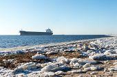 image of shipyard  - frozen beach near shipyard and sea port with rays of sun and wavebreaker - JPG
