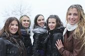 A Group of excited young girl friends outdoors in winter