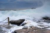 Bracing As Powerful Waves Come Crashing Over Rocks